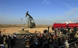 U.S. President Barack Obama delivers his speech as an oil jack pumps in the background.